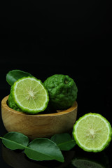 Kaffir Lime or Bergamot in wooden cup on black background with Copy Space for text.