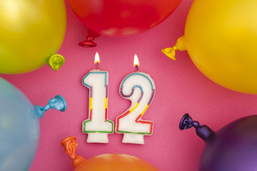 Happy Birthday number 12 celebration candle with colorful balloons