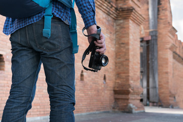 young asian man wearing blue shirt and jeans with camera and backpack standing near old brick wall