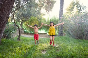 siblings running in sprinkler water