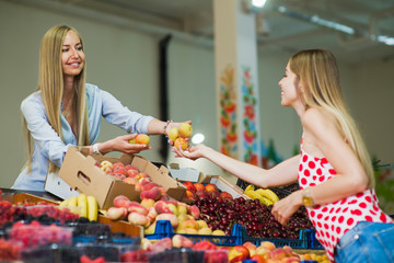 A woman buys fruits in the market. Woman seller is holding peaches in her hands. Focus on hand..