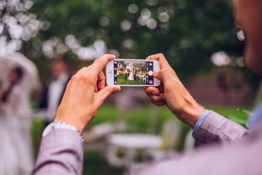 Man taking photo on phone of stylish wedding bride and groom posing. photo booth. wedding couple making photos with friends on phone camera. hand holding smartphone