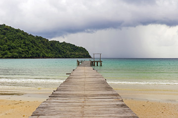 Wooden bridge extended into the sea with views of the tropical islands and the rain clouds coming.