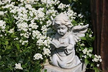 Engel auf einem Grab zwischen Blumen auf dem Friedhof
