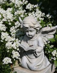 Engel zwischen weißen Blumen auf dem Friedhof