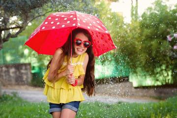 girl in splashing water under umbrella