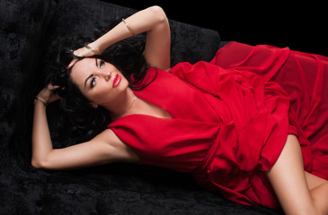 Portrait of sexy brunette in red dress on the black