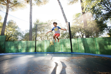 boy bouncing on trampoline
