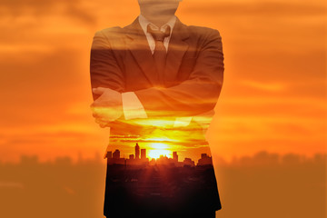 The Double exposure concept of business man with light sunset in city with building silhouette