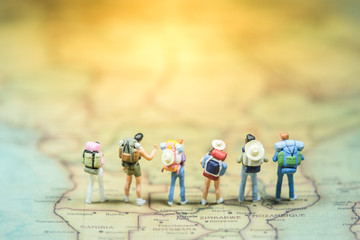 Selective focus. Miniature people : small traveler figures with backpack standing on South Africa Map / Geography of South Africa, exploring on earth background concept.
