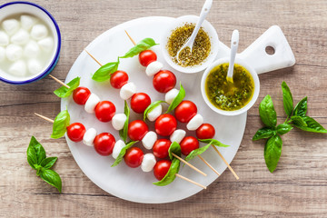 Appetizer in the form of caprese salad in the form of small shish kebabs for a summer healthy snack. On a wooden background