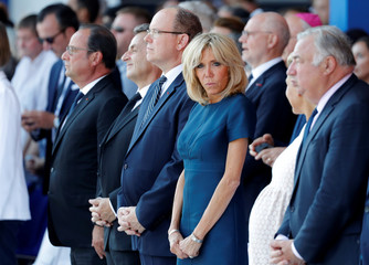 Brigitte Macron, wife of French President Emmanuel Macron, looks over at Laura Tenoudji, wife of Nice's mayor Christian Estrosi, as they attend the commemorative ceremony for last year's July 14 Bastille Day fatal truck attack on the Promenade des Anglais