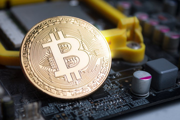 Close up shot gold Bitcoin on computer print circuit board shallow depth of field