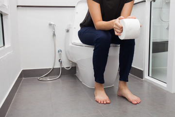 woman in bath towel sitting on toilet bowl
