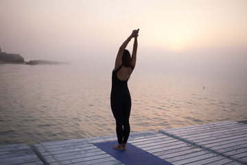 Fit woman in black sports wear posing in yoga asana on the beach