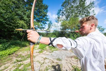 Bogenschießen - junger Mann hält Pfeil und Bogen