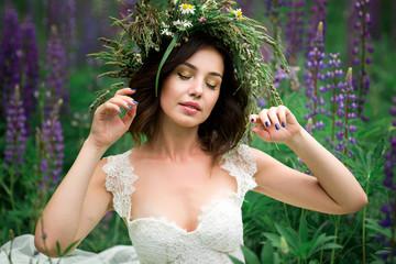 Beautiful girl in white dress in lupine field