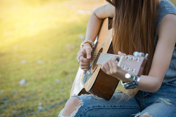 Young woman hands playing guitar acoustic song outdoor.