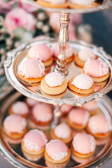 sweet bar with muffins cakes, sweets, fruits and candle holders in area of wedding party