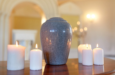 cremation urn and candles burning in church Wall mural