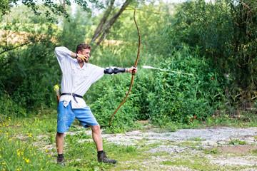 Junger Mann beim Bogenschießen mit fliegendem Pfeil