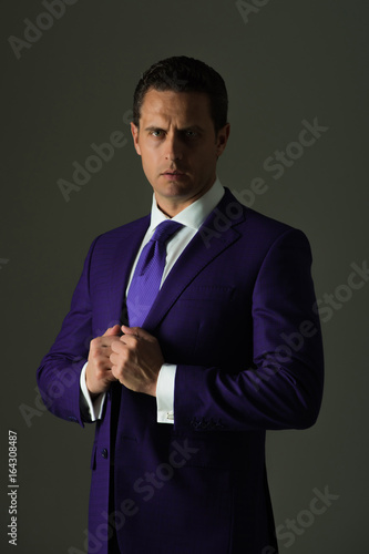 ee2e15cc6 Successful man adjusting tie in stylish blue formal suit