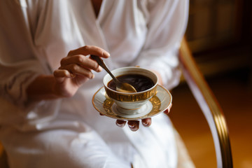 Happy young girl in a bathrobe drinking coffee in the morning in a wooden chair. Close view. Female hand stirring his coffee with a spoon