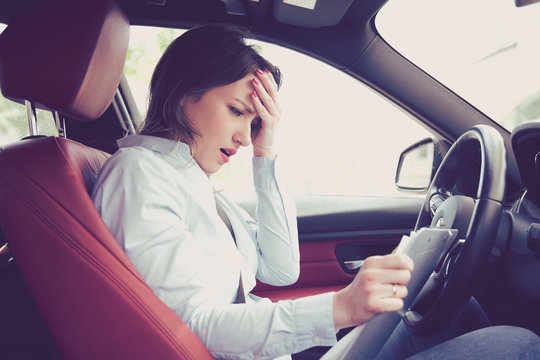 Stressed desperate woman driver with documents sitting inside her car