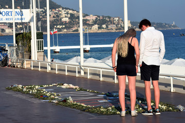 People look at a memorial with flowers, photos and texts to victims on the Promenade des Anglais as part of the commemorations of last year's July 14 Bastille Day fatal truck attack on the Promenade des Anglais in Nice