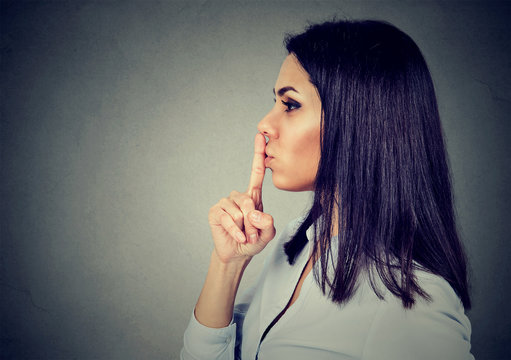 Business woman making silent sign with finger on lips.