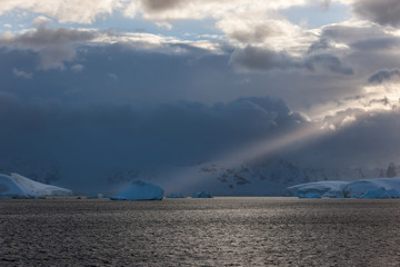 Stom clouds with light beam hitting icebergs along the Antarctic Peninsula.