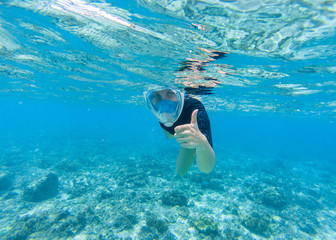 Woman snorkeling in turquoise sea water. Snorkel shows thumb in full face mask.
