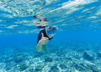 Woman snorkeling in shallow sea water. Snorkel shows thumb in full face mask.