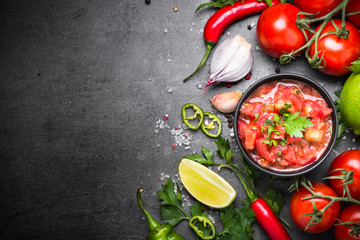 Traditional Latin American mexican salsa  sauce. Top view on black table.