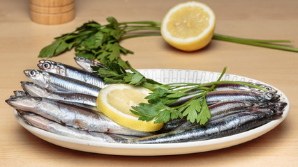 "Oval dish full of fresh Mediterranean anchovies, known as ""boquerones"" in Andalusian gastronomy, beside parsley and lemon slices. Mediterranean diet"