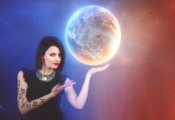 Astrology, horoscope. Charming brunette with a perceptive look on a cosmic background