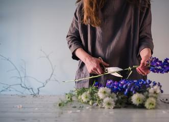 Frau schneidet am Abend Blumen für die Blumenvase