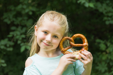 adorable young school age girl holding giant bavarian german pretzel outside in park