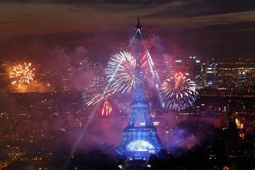 Fireworks explode in the sky above the Eiffel Tower, in a picture taken from the Montparnasse Tower Observation Deck, at the end of Bastille Day events in Paris