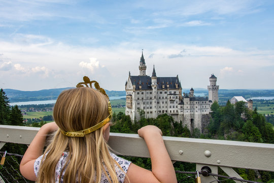 young girl looking out at fairy tale Neuschwanstein Castle in Germany
