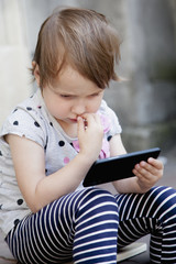 Social Media addiction. beautiful baby girl  holding phone (psychological problems, media mania, education)