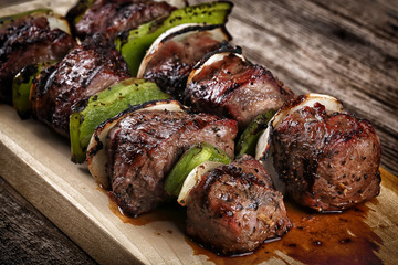 Cooked beef kebabs with vegetables and spices on wooden board