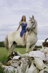 buffalo or bison skulls with brown haired girl riding bareback on white horse in field of green grass. Soft blue sky in vertical image with room for copy.