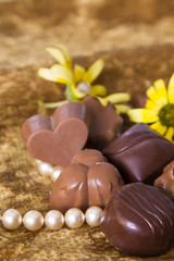 Chocolates and pearls on golden background