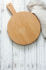 Wooden cutting board over white wood background