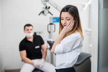 Beautiful woman suffering from terrible teeth pain, touching cheek with hand at dental clinic. Female feeling toothache. On the background dentist sitting on the chair. Dental care and health concept