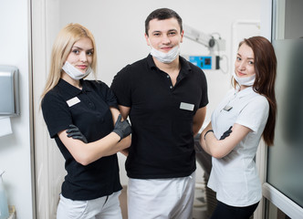 Portrait of male dentist and two female assistants in dental office. Women are standing with hands crossed and looking to the camera