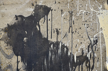 A photograph of a close-up of black paint spots on a concrete wall. Pouring paint on the wall in random order. The concept of graffiti and street art culture