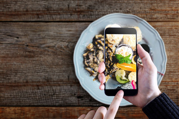 Snap before Eat concept, Lifestyle of Urban people, Top view of Hand pressing Smart Phone button to take photo of Dessert Plate on wooden table