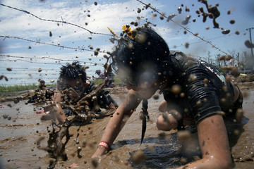 Participants take part at a mud run race in Shanghai